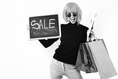 Dziewczyna w peruki mienia pakunku, wieszaki, deska z sprzedaży inskrypcją obraz stock