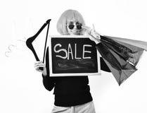Dziewczyna w peruki mienia pakunku, wieszaki, deska z sprzedaży inskrypcją zdjęcia stock