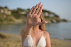 Dziewczyna w plaży z jego ręką podnoszącą w górę przerwa gesta wewnątrz obrazy stock