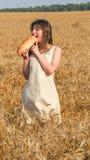 Dziewczyna w polu gryźć bochenek chleb Zdjęcie Stock