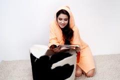 Dziewczyna w pomarańczowego bathrobe czytelniczym magazynie w domu zdjęcie stock