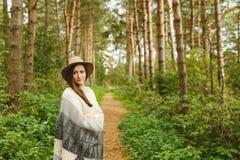 Dziewczyna w poncho i kapeluszu w lesie fotografia royalty free