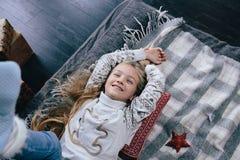 Dziewczyna w pulowerze na łóżku na zima dniu Dziewczyna ma zabawę w domu Zdjęcia Stock
