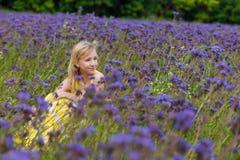 Dziewczyna w purpurach kwitnie outdoors w lecie Zdjęcie Royalty Free