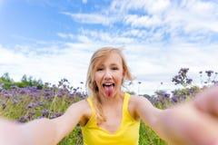 Dziewczyna w purpurach kwitnie outdoors w lecie Zdjęcia Royalty Free