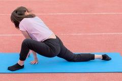 Dziewczyna w różowej koszulce czarnych spodniach i wykonuje sprawności fizycznych ćwiczenia w na wolnym powietrzu widok z powrote obrazy royalty free