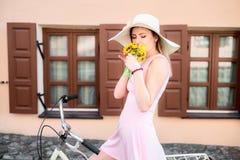 Dziewczyna w różowej sukni w kapeluszu na bicyklu wącha perfumowanie kwiaty zdjęcia royalty free