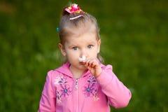 Dziewczyna w różowym bluzki obwąchaniu kwitnie Fotografia Royalty Free