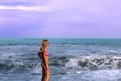 Dziewczyna w różowym kostiumu kąpielowym stoi morzem zdjęcia stock