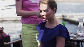 Dziewczyna w różowym koszulowym tkactwo warkoczu młoda kobieta w błękit sukni taras uśmiech zdjęcie wideo