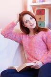 Dziewczyna w różowym pulowerze z książką Zdjęcie Stock