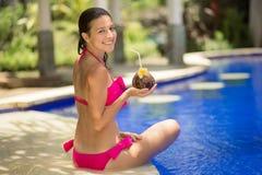 Dziewczyna w różowym swimsuit jest odpoczynkowa na krawędzi basenu z napojem od koksu obrazy royalty free