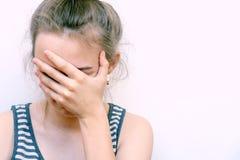 Dziewczyna w rozpaczu zakrywa jej twarz z ręką Zaakcentowanej kobiety migreny b?lowy ?e?ski portret w domu fotografia stock
