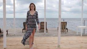Dziewczyna w rozwija odziewać w wiatrze na nabrzeżu, młoda kobieta iść bosonogą na drewnianym molu, dama w eyeglasses zdjęcie wideo