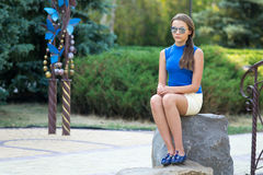 Dziewczyna w słońc szkłach z długim włosy i siedzi na kamieniu obraz royalty free