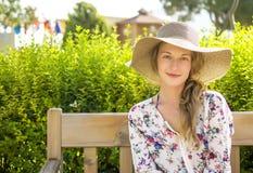 Dziewczyna w słomianego kapeluszu obsiadaniu na ławce Obrazy Royalty Free