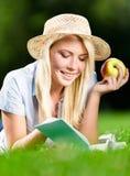 Dziewczyna w słomianym kapeluszu z jabłkiem czyta książkę na zielonej trawie Fotografia Royalty Free