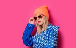 Dziewczyna w 90s sportów kapeluszu z okularami przeciwsłonecznymi i kurtce obrazy stock