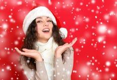 Dziewczyna w Santa kapeluszowym portrecie na czerwonego koloru tle, bożego narodzenia wakacyjnym pojęciu, szczęśliwy, i emocje Fotografia Royalty Free