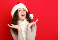 Dziewczyna w Santa kapeluszowym portrecie na czerwonego koloru tle, bożego narodzenia wakacyjnym pojęciu, szczęśliwy, i emocje Zdjęcia Royalty Free