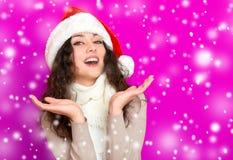 Dziewczyna w Santa kapeluszowym portrecie na menchiach barwi tło, bożego narodzenia wakacyjnego pojęcie, szczęśliwy, i emocje Zdjęcia Stock