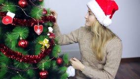 Dziewczyna w Santa nakrętce dekoruje choinki zdjęcie wideo