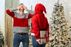 Dziewczyna w Santa pulowerze dostaje gotową dawać prezentowi i facet czekać na zakrywający jego oczy z jego rękami obraz stock