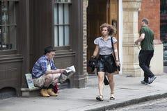 Dziewczyna w skóry spódnicie iść za bezdomnym mężczyzna który sprzedaje magazin Fotografia Stock