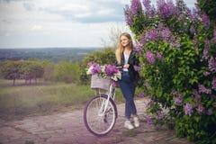 Dziewczyna w skórzanej kurtce blisko białego bicyklu zdjęcie royalty free