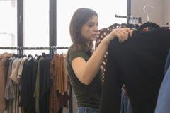Dziewczyna w sklepie odzieżowym wybiera czarną kurtkę obrazy stock