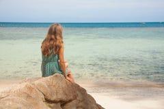 Dziewczyna w smokingowym obsiadaniu na skale morzem zdjęcie stock