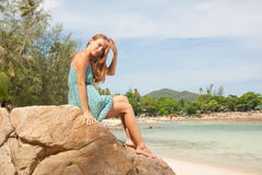 Dziewczyna w smokingowym obsiadaniu na skale morzem obrazy stock
