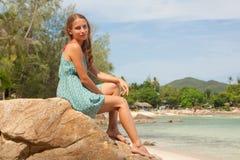 Dziewczyna w smokingowym obsiadaniu na skale morzem fotografia royalty free
