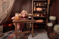 Dziewczyna w smokingowym obsiadaniu w sklepie spożywczym Fotografia Royalty Free