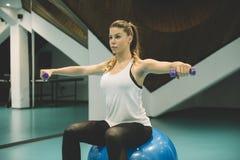 Dziewczyna w sporta kostiumu robi fizycznym ćwiczeniom z dumbells zdjęcia royalty free