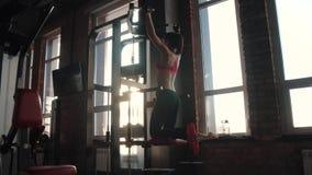 Dziewczyna w sportswear trenuje w gym sportsmenka ono ciągnie up na barze zbiory wideo