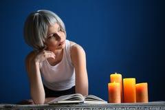 Dziewczyna w srebnej peruce pozuje z książką i świeczkami z bliska niebieska tła Fotografia Stock