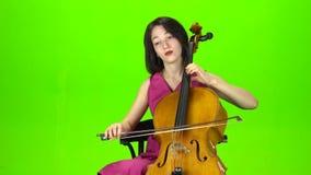 Dziewczyna w sukni bawić się wiolonczelę zielony ekran zbiory wideo