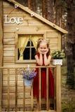 Dziewczyna w sukni czerwonych pozach w drzewnym domu Obraz Stock