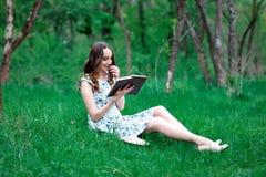 Dziewczyna w sukni z książką w parku lub kobieta, siedzimy na Zdjęcie Stock