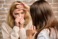 Dziewczyna w szalika chwyta tkance podczas gdy lekarka egzamininuje ona Rozpoznaje objawy zimno Remedia muszą pomagać bić zimno p obrazy royalty free