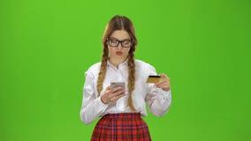 Dziewczyna w szkłach wybiera numer liczby na telefonie z złoto kartą zielony ekran zbiory