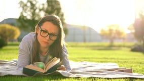 Dziewczyna w szkło czytelniczej książce łgarski puszek na koc w parku przy zmierzchem zbiory