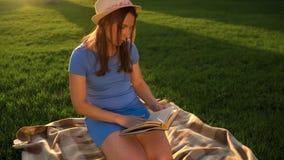 Dziewczyna w szkło czytelniczej książki obsiadaniu na koc w parku przy zmierzchem zbiory