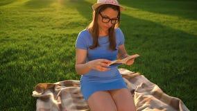 Dziewczyna w szkło czytelniczej książki obsiadaniu na koc w parku przy zmierzchem zdjęcie wideo
