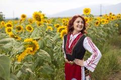 Dziewczyna w tradycyjnej Bułgarskiej sukni w polu słoneczniki zdjęcia royalty free