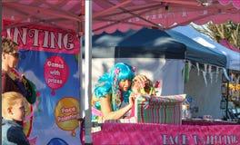 Dziewczyna w turkusowy peruki malować dziewczyny stawia czoło w twarz obrazu budka z matką i siostrzanym patrzeć dalej w Redlands zdjęcie royalty free