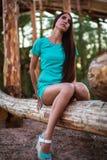 Dziewczyna w turkusu skrótu sukni obsiadaniu na drzewnej beli zdjęcie stock