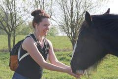 Dziewczyna w wiosny łące karmi konia Za plecakiem, słuchawki w ucho obraz stock