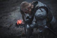 Dziewczyna w wizerunku Jeanne d ` łuk klęczy w opancerzeniu, z kordzikiem w jej rękach przeciw tłu i ogień i dym Zdjęcia Royalty Free